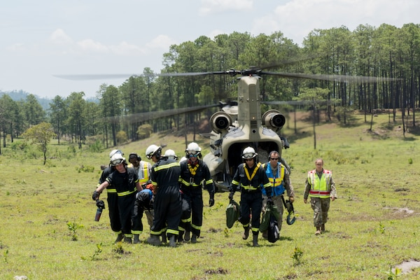A group of 612th Air Base Squadron firefighters carry equipment from a CH-47 Chinook to the site of a simulated aircraft crash during a search and rescue exercise, May 21, 2019, in Comayagua, Honduras. Members from various units on Joint Task Force – Bravo participated in the exercise that simulated a HH-60 Blackhawk crashed during a routine flight carrying personnel. The exercise practiced notification, recall, search and rescue, on-scene medical care, recovery of personnel from low and high angle austere terrain, and medical care once the injured returned to base. (U.S. Air Force photo by Staff Sgt. Eric Summers Jr.)