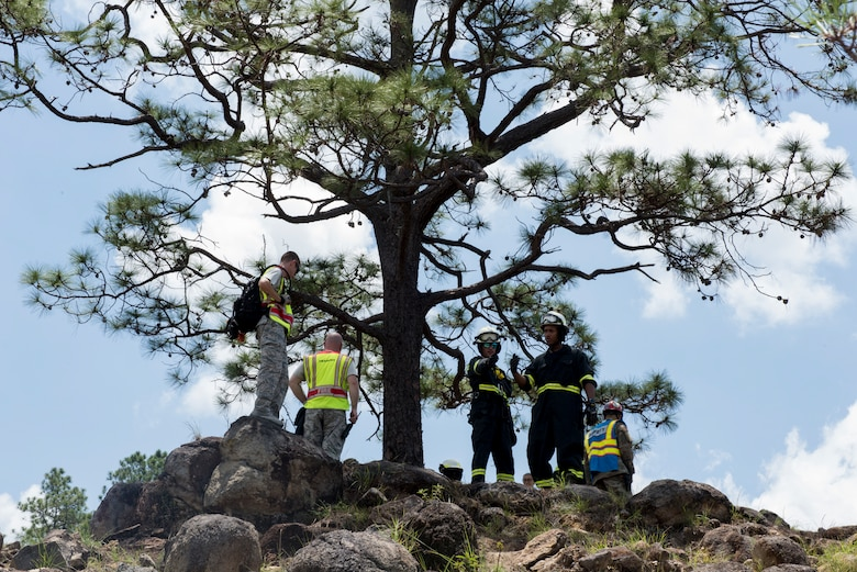 A group of 612th Air Base Squadron firefighters survey a slope where a simulated aircraft crash casualty is located during a search and rescue exercise, May 21, 2019, in Comayagua, Honduras. Members from various units on Joint Task Force – Bravo participated in the exercise that simulated a HH-60 Blackhawk crashed during a routine flight carrying personnel. The exercise practiced notification, recall, search and rescue, on-scene medical care, recovery of personnel from low and high angle austere terrain, and medical care once the injured returned to base. (U.S. Air Force photo by Staff Sgt. Eric Summers Jr.)