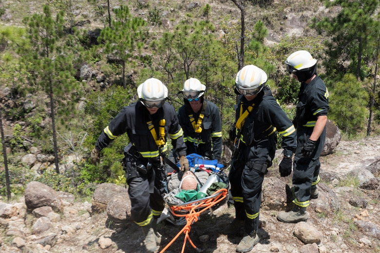 A group of Airmen from the 612th Air Base Squadron haul a simulated patient up a hill during a search and rescue exercise, May 21, 2019, in Comayagua, Honduras. Members from various units on Joint Task Force – Bravo participated in the exercise that simulated a HH-60 Blackhawk crashed during a routine flight carrying personnel. The exercise practiced notification, recall, search and rescue, on-scene medical care, recovery of personnel from low and high angle austere terrain, and medical care once the injured returned to base. (U.S. Air Force photo by Staff Sgt. Eric Summers Jr.)