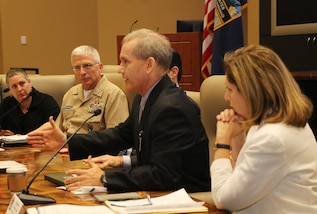U.S. Navy Adm. Craig Faller listens to Steve Olive, Acting Assistant Administrator for USAID.