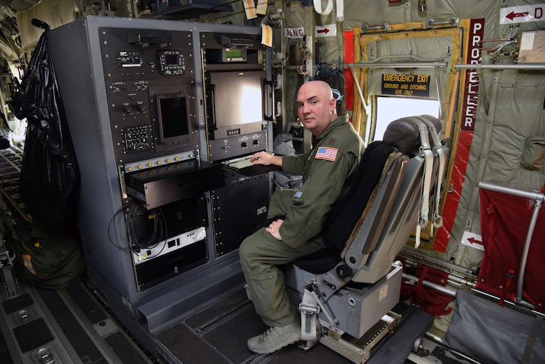 Maj. Tobi Baker, 53rd Weather Reconnaissance Squadron aerial weather reconnaissance officer, poses for a photo at the ARWO station inside of a WC-130J Super Hercules at Keesler Air Force Base, Mississippi, May 23, 2019. The ARWO acts like a flight director in a storm. He continuously monitors atmospheric data collected from the aircraft's sensors throughout the mission. The gathered data is checked for accuracy and the information is used to guide the aircraft into the center of the storm. (U.S. Air Force photo by Tech. Sgt. Christopher Carranza)