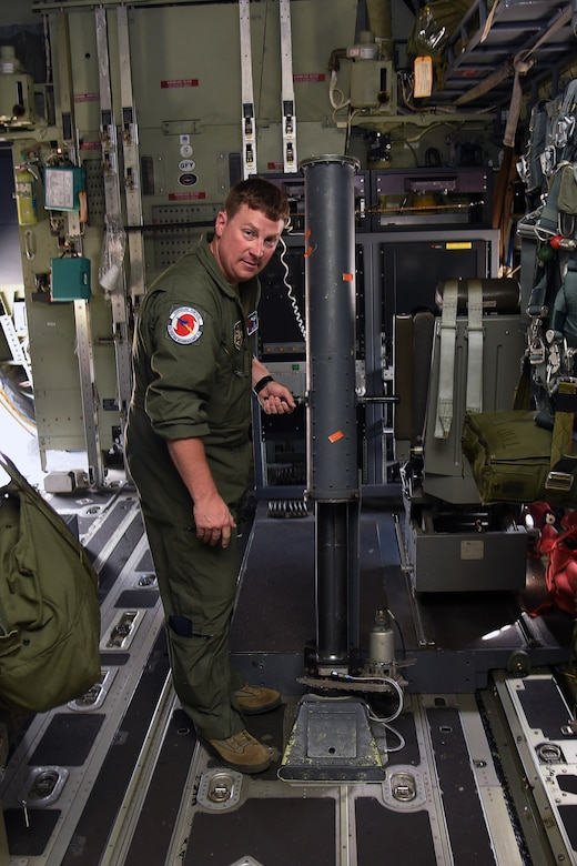 Master Sgt. Chris Becvar, 53rd Weather Reconnaissance Squadron loadmaster, demonstrates the dropsonde tube operations inside of a WC-103J Super Hercules at Keesler Air Force Base, Mississippi, May 23, 2019. The loadmaster, who doubles as a dropsonde operator launches the parachute-rigged device from the aircraft using the tube. (U.S. Air Force photo by Tech. Sgt. Christopher Carranza)