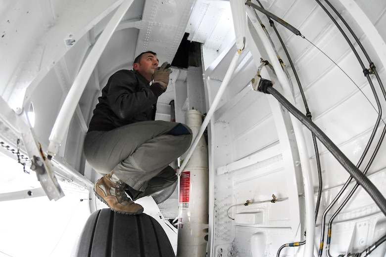 Master Sgt. Allen Clutter, a flight engineer attached to 514th Flight Test Squadron, inspects inside the wheel well while performing a pre-flight functional flight check on a U.S. Navy C-130 Hercules April 11, 2019, at Hill Air Force Base, Utah. (U.S. Air Force photo by Cynthia Griggs)