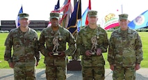 The newly awarded CASCOM Best Warrior winners – Staff Sgt. Japheth Edwards, Echo Company, 16th Ordnance Battalion; and Spc. Colby Matthews, 508th Transportation Co., 266th Quartermaster Bn. – pose with statuettes presented by Command Sgt. Maj. Michael Perry III, CASCOM CSM, and Maj. Gen. Rodney D. Fogg, CASCOM and Fort Lee commanding general, during an outdoor ceremony May 23 in front of the CASCOM headquarters.  The two along with three others competed in the Soldier skills competition featuring several technical, tactical and administrative events over three days.