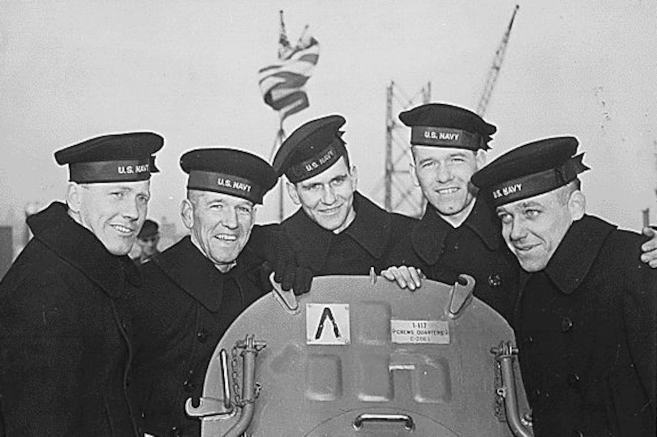 Five sailors stand and smile for a photo.