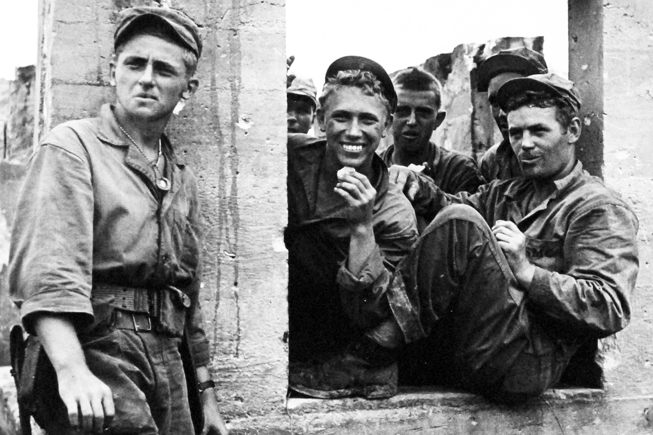 Marines smile and pose for a photo by a cement-type wall.