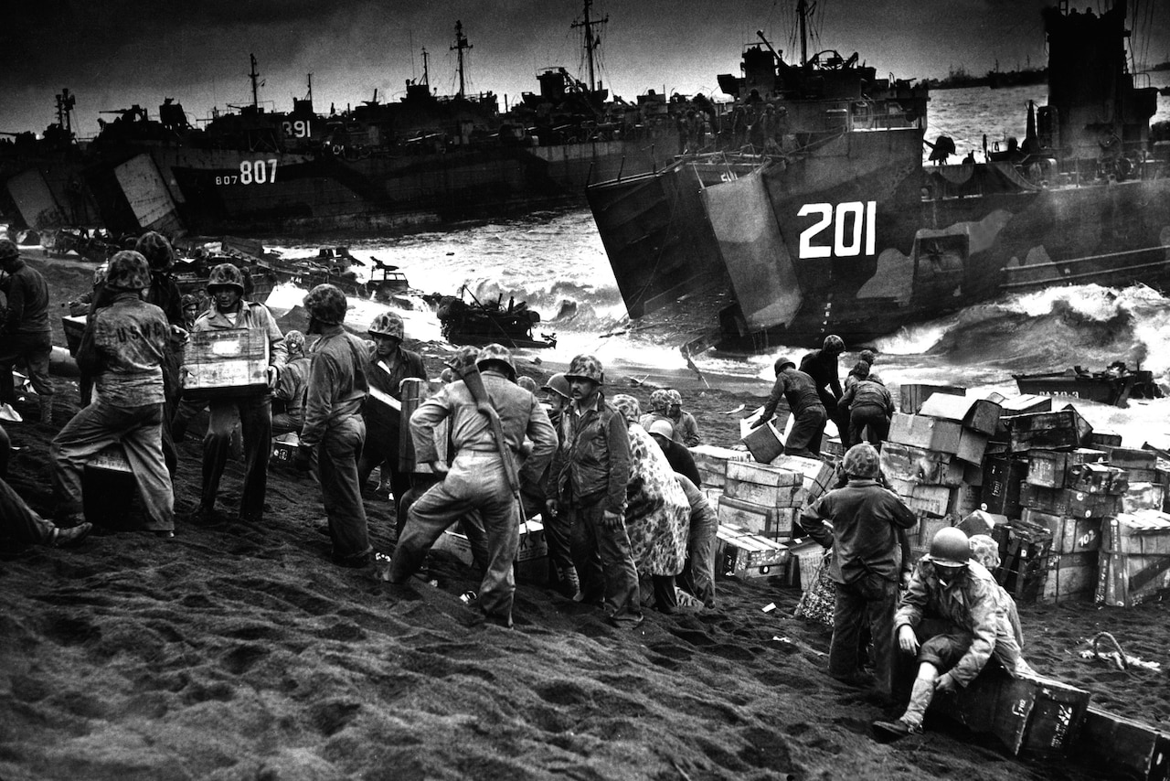 Troops and ships arrive on a beach.