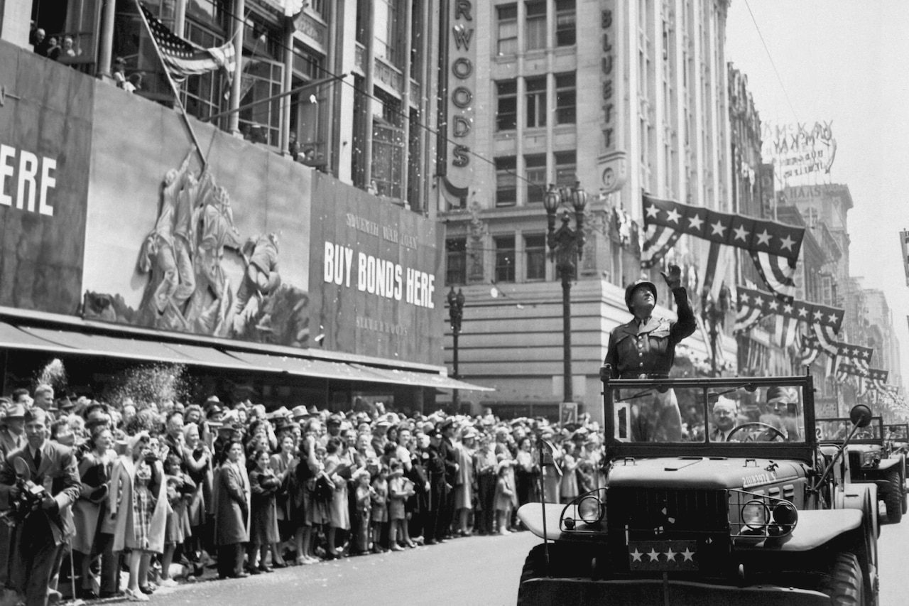 Army Gen. George S. Patton stands and waves from an open jeep as people line a downtown street.