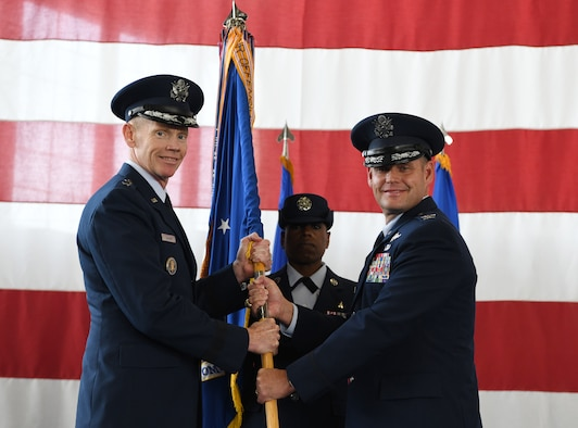Maj. Gen. James Dawkins Jr., the 8th Air Force commander, passes the guidon to Col. David A. Doss, the incoming 28th Bomb Wing commander, during a change of command ceremony at the PRIDE Hangar on Ellsworth Air Force Base, S.D., May 30, 2019. As commander, Doss will take over responsibility of 27 B-1B Lancers and more than 3,700 total-force Airmen. (U.S. Air Force photo by Senior Airman Thomas Karol)