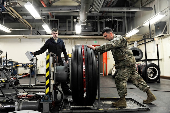 U.S. Air Force Senior Airman Nathan Strickland, wheel and tire technician assigned to the 18th Equipment Maintenance Squadron, places an aircraft wheel onto a wheel clamp at Kadena Air Base, Japan, May 22, 2019.