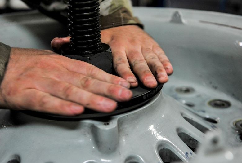 U.S. Air Force Senior Airman Nathan Strickland, wheel and tire technician assigned to the 18th Equipment Maintenance Squadron, tightens the bolts on an aircraft wheel at Kadena Air Base, Japan, May 22, 2019.