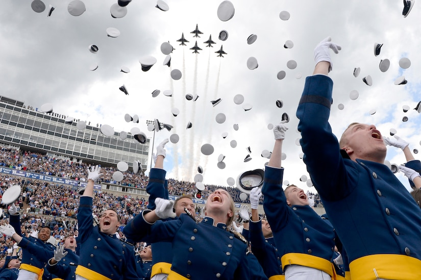 A group of graduates toss hats in the air as aircraft fly over a stadium.