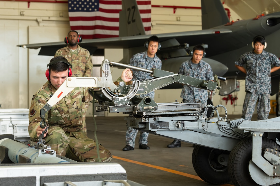 U.S. Air Force Senior Airman Jairo Villa, 18th Maintenance Group weapons lead crew member, guides a weapon loader during the first bilateral weapons load exchange between Kadena Air Base and the Japan Air Self-Defense Force, May 23, 2019. The goal of the training is to accurately and safely load munitions while strengthening the U.S.-Japan alliance in order to secure a free-and-open Indo-Pacific. (U.S. Air Force photo by Airman 1st Class Matthew Seefeldt)