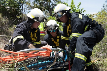 Firefighters from the 612th Air Base Squadron strap in a simulated aircraft patient that fell down a steep slope during search and rescue exercise, May 21, 2019, in Comayagua, Honduras. Members from various units on Joint Task Force – Bravo participated in the exercise that simulated a HH-60 Blackhawk crashed during a routine flight carrying personnel. The exercise practiced notification, recall, search and rescue, on-scene medical care, recovery of personnel from low and high angle austere terrain, and medical care once the injured returned to base. (U.S. Air Force photo by Staff Sgt. Eric Summers Jr.)