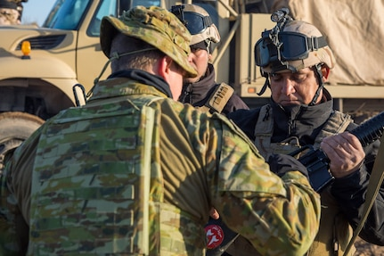 An Australian soldier from Task Group Taji 8 inspects and clears an Iraqi Army (IA) soldier's weapon before a School of Infantry NCO 2 (SINCO 2) led culminating activity at Taji Military Complex, Iraq, Jan. 20, 2019. The event was the final test for four IA battalions that have received 10 weeks' training from the SINCO2 with oversight from Australian Army instructor assessors from Task Group Taji 8. The Coalition offers training programs include courses in areas as diverse as operational planning, counter-terrorism, logistics and sustainment, equipment maintenance, counter-IED techniques and law enforcement. The Iraqi Army School of Infantry NCO 2 recently achieved initial operating capability, meaning that the school can perform 75 percent of its operations without Coalition assistance.