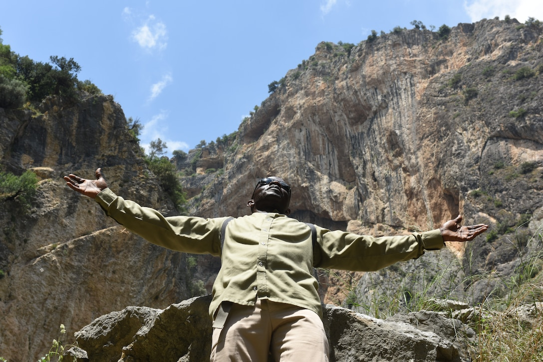 Capt. John Appiah, 39th Air Base Wing chaplain, raises his hands toward the sky at Kapikaya Canyon during an outdoor recreation trip on May 25, 2019, in Adana, Turkey. Several resources are available to help Airmen decompress from stressors such as the Air Force's Outdoor Recreation program, which gives military members and civilian employees a chance to experience Turkish culture. (U.S. Air Force photo by Senior Airman Joshua Magbanua)