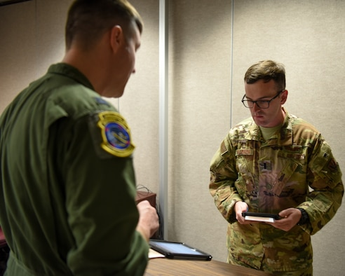 Capt. Kenneth Gilbert, 348th Reconnaissance Squadron RQ-4 chief pilot informs 1st Lt. Christopher Waldron, RQ-4 mission commander, of the unit's electronic flight books capabilities May 13, 2019 at Grand Forks Air Force Base, North Dakota. Gilbert manages the installation's EFB program, which is the test-bed for EFB implementation with remotely piloted aircraft in the United States Air Force.  (U.S. Air Force photo by Senior Airman Elijaih Tiggs)