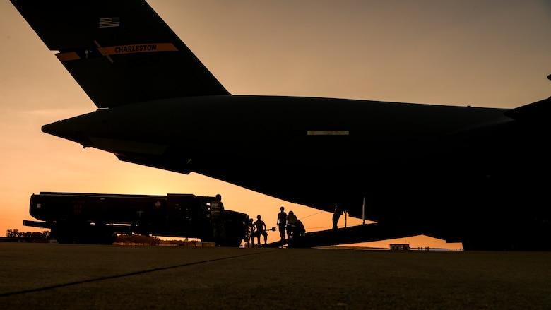 Airmen winch an R-11 refueler aboard a C-17 Globemaste