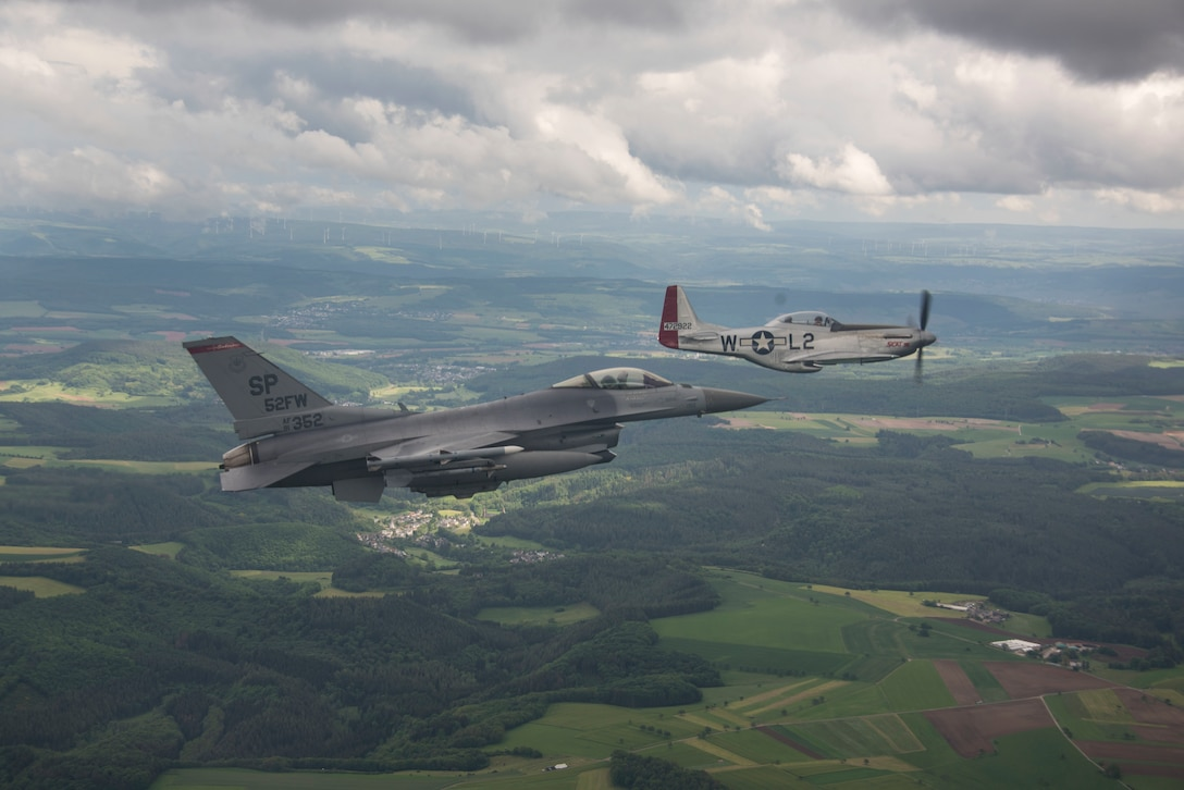a P-51 Mustang flies along an F-16C Fighting Falcon
