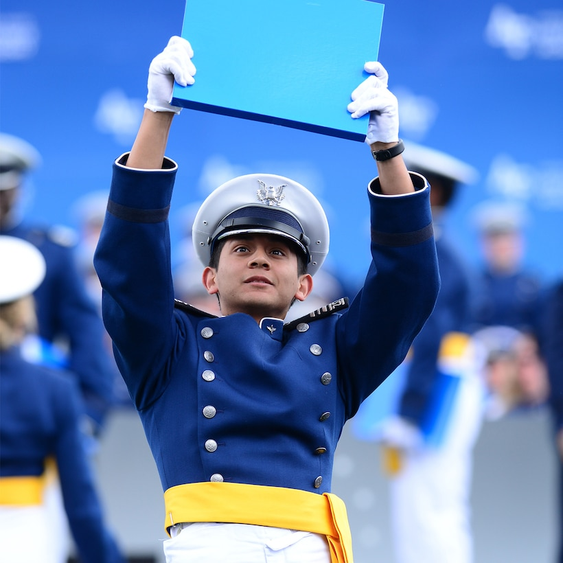 A graduate of the U.S. Air Force Academy holds up a diploma.