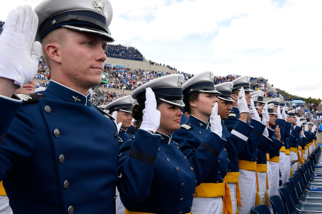 Cadets stand and salute during graduation.