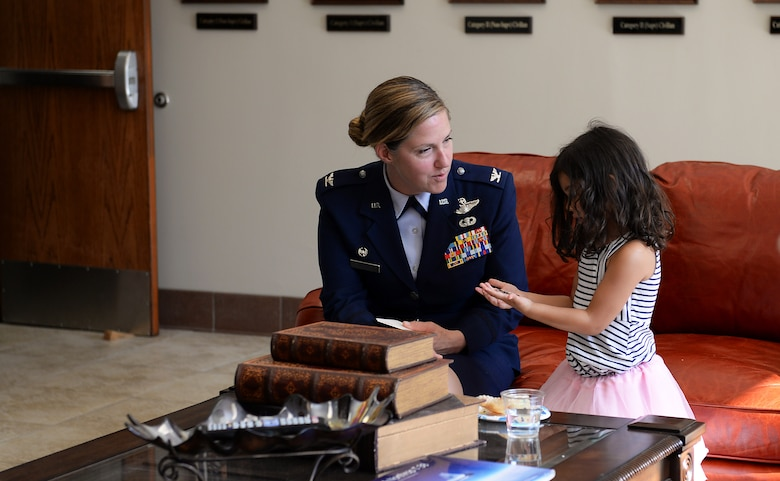"""Col. Samantha Weeks, 14 Flying Training Wing commander, gives Aeliana, daughter of 1st Lt. David Albandoz, 198th Airlift Squadron C-130H pilot, Puerto Rico a coin after a Memorial Day Ceremony May 28, 2019, on Columbus Air Force Base, Miss. Aeliana visited Columbus AFB with her mother, Nicoleta Padureanu, to attend a Memorial Day Ceremony in honor of her late father where his name was unveiled on the memorial wall in the Richard """"Gene"""" Smith Plaza. (U.S. Air Force photo by Airman 1st Class Hannah Bean)"""