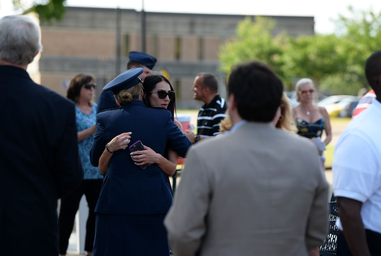"""Col. Samantha Weeks, 14 Flying Training Wing commander, hugs Nicoleta Padureanu, widow of 1st Lt. David Albandoz, 198th Airlift Squadron C-130 Hercules pilot, Puerto Rico during a Memorial Day Ceremony May 28, 2019, at the Richard """"Gene"""" Smith Plaza on Columbus Air Force Base, Miss. Nicoleta and her daughter, Aeliana, visited Columbus AFB to attend a Memorial Day Ceremony in his honor where his name was unveiled on the memorial wall in the Richard """"Gene"""" Smith Plaza. (U.S. Air Force photo by Airman 1st Class Hannah Bean)"""