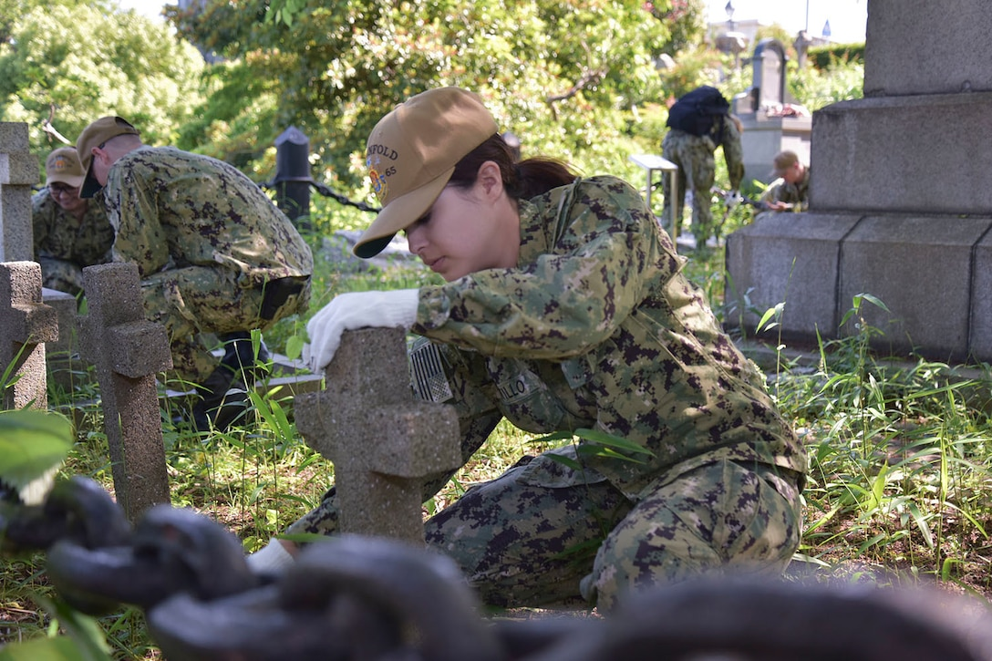 Sailors clean tombstones in a cemetery.