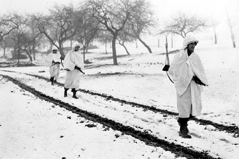 Three service members wearing white sheets walk across a snow-covered field.