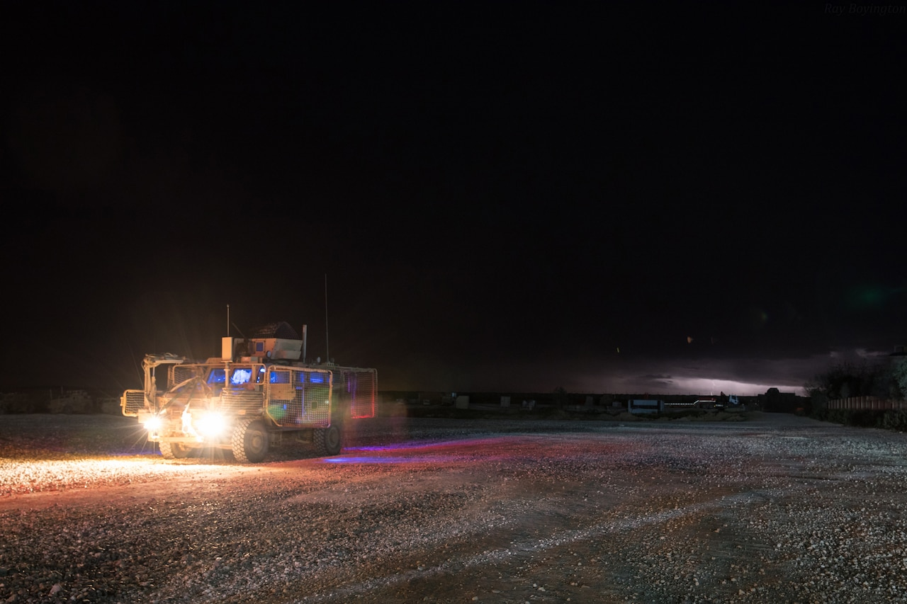 A military combat vehicle moves across a gravel yard in the dark of night.