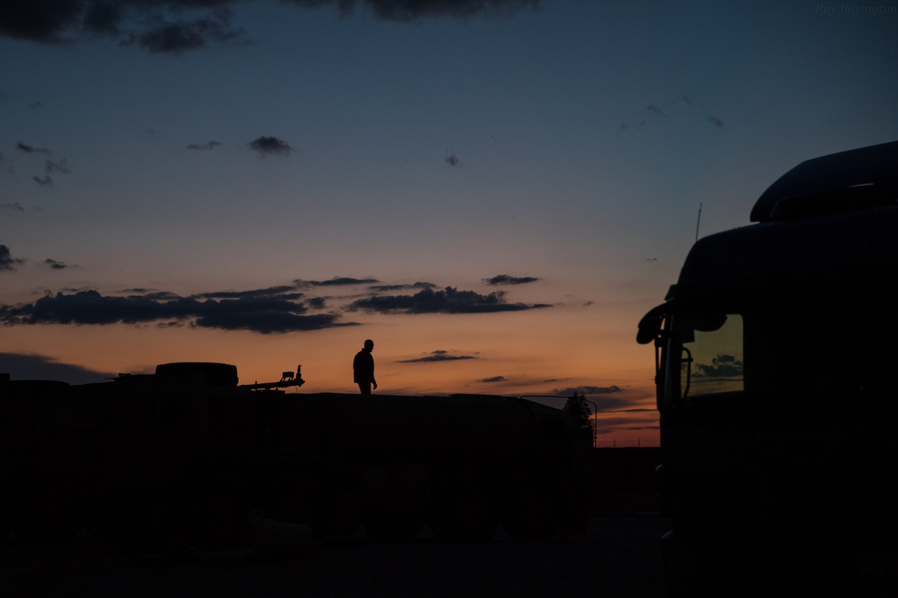 A service member stands in silhouette at dusk against an orange and blue sky.