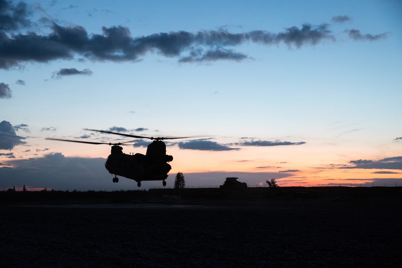A helicopter with two rotors lifts off the ground in silhouette.
