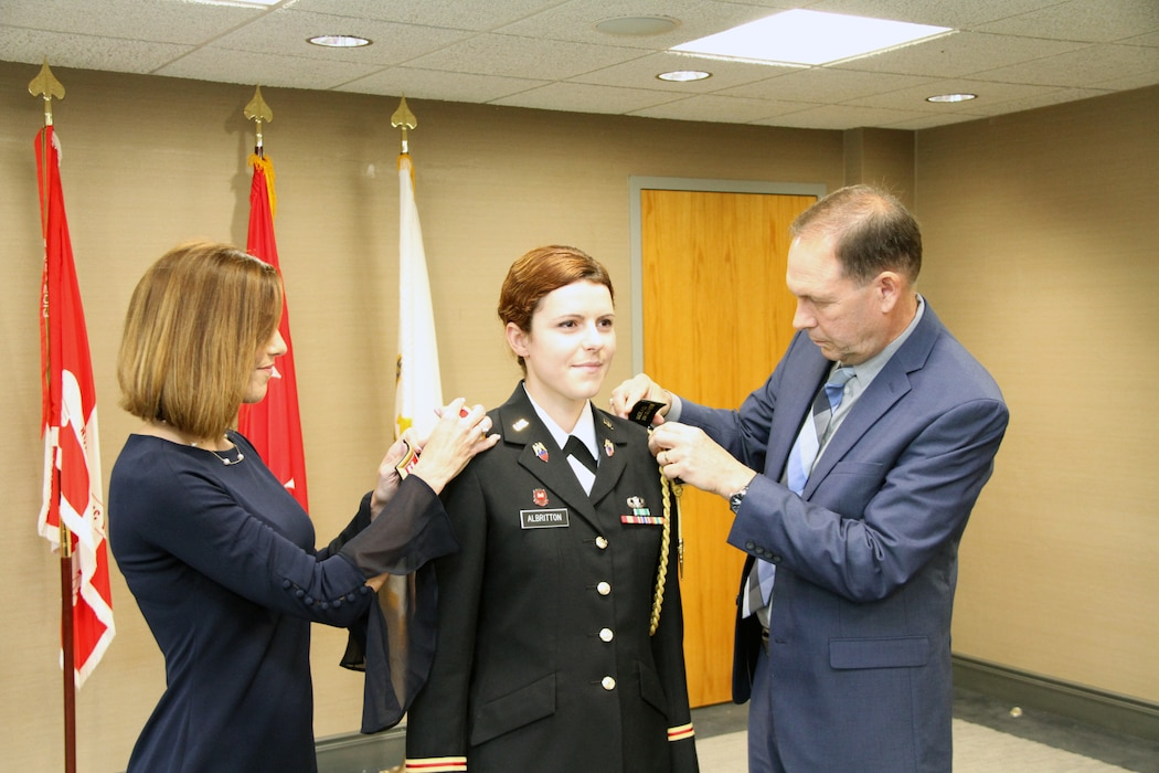 Capt. Shirley Albritton's parents Frankie and Angela replace her first lieutenant shoulder boards with her new rank at a promotion ceremony at Fort Hamilton on May 30, 2019.