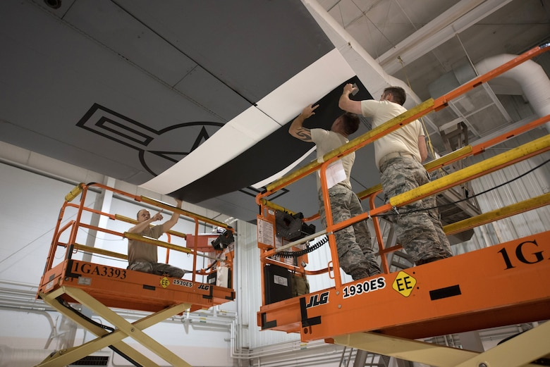 Members of the 123rd Maintenance Squadron apply decals to a 123rd Airlift Wing C-130 Hercules at the Kentucky Air National Guard Base in Louisville, Ky., May 14, 2019. The C-130 will fly in the 75th anniversary of D-Day over Normandy, France, in June. (U.S. Air National Guard photo by Phil Speck)