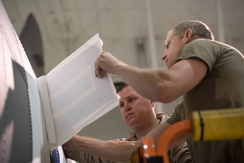 Tech. Sgt. Derek Clow (right), 123rd Maintenance Squadron structural repair technician, and Tech. Sgt. Tyler Shoffner, 123rd Maintenance Squadron metals technician, apply an Air Force roundel decal to a 123rd Airlift Wing C-130 Hercules at the Kentucky Air National Guard Base in Louisville, Ky., May 15, 2019. The C-130 will fly in the 75th anniversary of D-Day over Normandy, France, in June. (U.S. Air National Guard photo by Phil Speck)