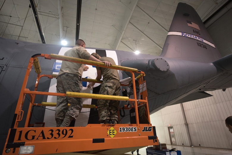 Tech. Sgt. Derek Clow, 123rd Maintenance Squadron structural repair technician, and Tech. Sgt. Tyler Shoffner, 123rd Maintenance Squadron metals technician, apply an Air Force roundel decal to a 123rd Airlift Wing C-130 Hercules at the Kentucky Air National Guard Base in Louisville, Ky., May 15, 2019. The C-130 will fly in the 75th anniversary of D-Day over Normandy, France, in June. (U.S. Air National Guard photo by Phil Speck)