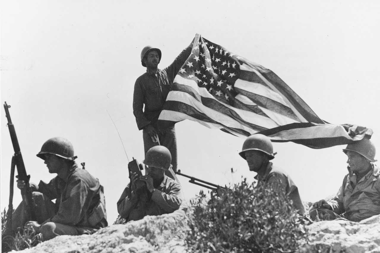 A soldier holds a flag up on a mountaintop as others crouch around him.
