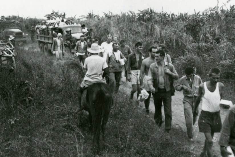 People in civilian clothes walk on a path with a truck in the rear and someone on horseback beside them.