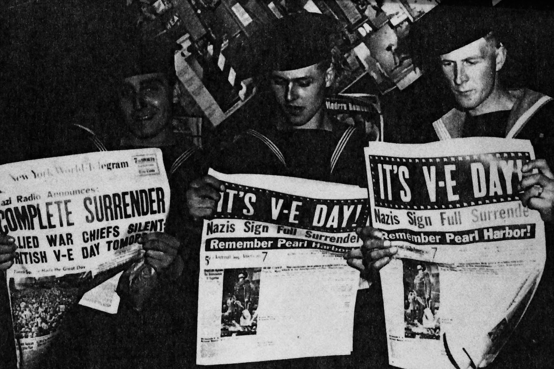 Three sailors read newspapers with giant 'It's V-E Day!' headlines.