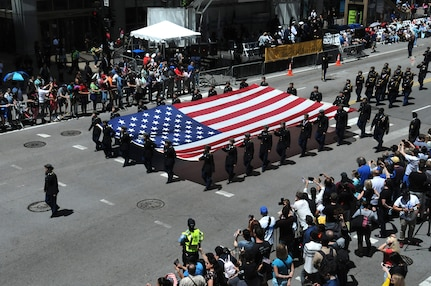 Chicago high school junior ROTC cadets carry a large flag during the City of Chicago Memorial Day parade, Mar. 25, 2019.