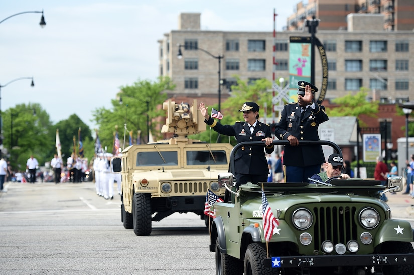 Brig. Gen. Kris Belanger, left, Commanding General, 85th U.S. Army Reserve Support Command, with Command Sgt. Maj. Theodore Dewitt, Command Sergeant Major, 85th USARSC, wave at a crowd during the Village of Arlington Heights Memorial Day parade, Mar. 27, 2019.