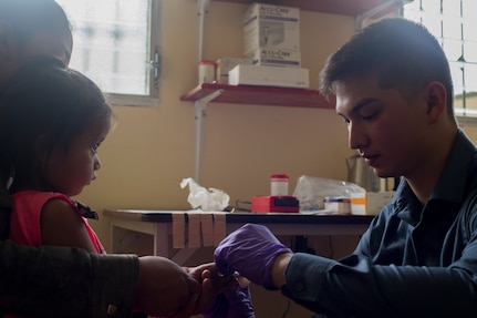 U.S. Army Spc. Colin Yap, Joint Task Force – Bravo Medical Element medic, pricks the finger of young girl to measure her hemoglobin levels during a Pediatric Medical Readiness Training Exercise May 23, 2019 in La Paz, Honduras. MEDRET missions allow JTF-B medical personnel to train in their areas of expertise, while providing a service and strengthening partnership with the host nation. The service members saw approximately 120 patients during the mission. (U.S. Air Force photo by Staff Sgt. Eric Summers Jr.)