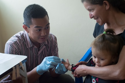 U.S. Army Spc. Alec Pagtakhan, Joint Task Force – Bravo Medical Element EMT medic, gathers a blood sample to check the child's hemoglobin levels during a Pediatric Medical Readiness Training Exercise May 23, 2019 in La Paz, Honduras. MEDRET missions allow JTF-B medical personnel to train in their areas of expertise, while providing a service and strengthening partnership with the host nation. The service members saw approximately 120 patients during the mission. (U.S. Air Force photo by Staff Sgt. Eric Summers Jr.)