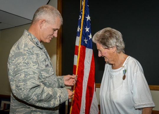Col. Lawrence Havird, 412th Maintenance Group Commander, presents commander's coins to Patricia Henrich during her retirement ceremony at Edwards Air Force Base, Calif., May 31. Henrich retired after 67 years of federal civilian service. (U.S. Air Force photo by Giancarlo Casem)