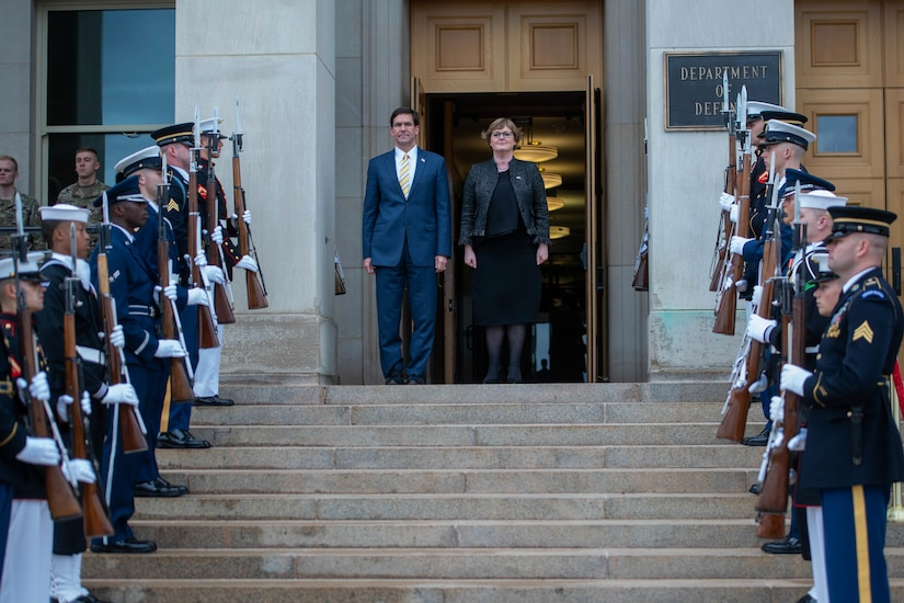 A man and woman stand at the top of steps, uniformed military personnel line the steps.