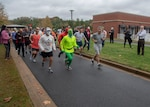 Male and female runners and walkers begin the Halloween-themed 5K.