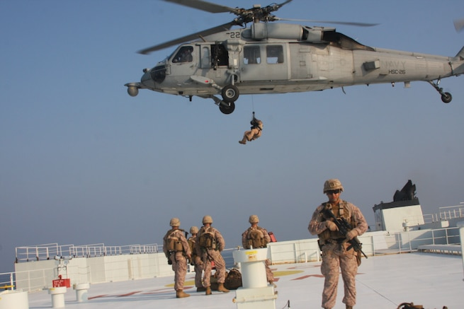 Marines assigned to Fleet Anti-Terrorism Security Team, Central Command (FASTCENT) prepare to be extracted by a Navy MH-60S Seahawk, attached to Helicopter Sea Combat Squadron 26 (HSC-26) from the Arc Liberty, a Military Sealift Command time chartered vessel, after providing security during a Strait of Hormuz transit. FASTCENT Marines work with U.S. partners and allies to protect personnel and property while simultaneously ensuring freedom of navigation in international waterways. Task Force 51 and 5th Marine Expeditionary Brigade is entrusted with rapidly aggregating crisis response capabilities and positioning Navy and Marine Corps forces throughout the U.S. Central Command area of responsibility to ensure command and control of forces at sea, from the sea, and ashore. (Photo by Marine Corps Cpl. Tanner A. Gerst)