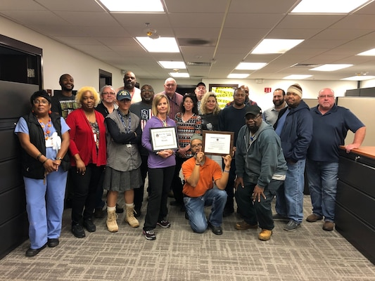 DLA Disposition Services at Fort Meade team pose with two certificate awards