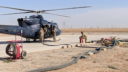 Spc. Clara Zurita, motor transport operator, and Spc. Godswill Orzabal, petroleum supply specialist, 574th Composite Supply Company, fuel up an NH90 helicopter at Erbil, Iraq, Oct. 15, 2019.