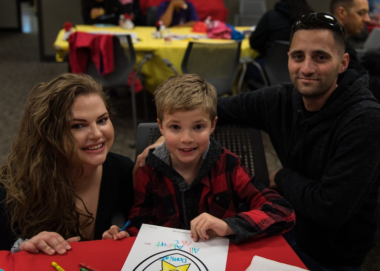 Airman 1st Class Joshua Bruner (right), 26th Operational Weather Squadron weather forecaster, poses for a photo with his wife, Deana (left) and his son, Dominic (middle), during the Exceptional Family Member Program's Dinner with Sparky at Barksdale Air Force Base, La., Oct. 11, 2019. (U.S. Air Force photo by Airman 1st Class Lillian Miller)